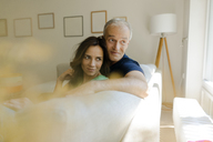Smiling mature couple sitting on couch at home - KNSF04605