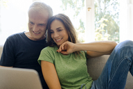Smiling mature couple sitting on couch at home sharing laptop - KNSF04608