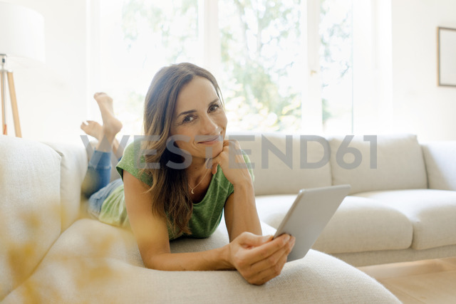 Portrait of smiling mature woman lying on couch at home using tablet - KNSF04614