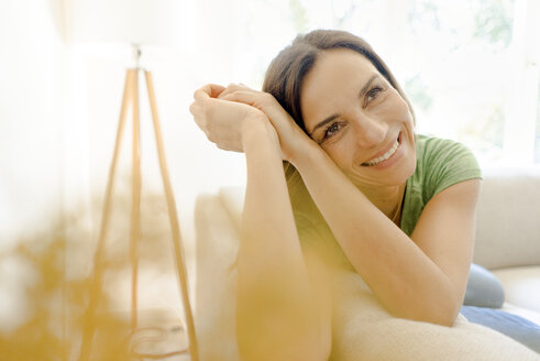 Portrait of smiling mature woman lying on couch at home - KNSF04617