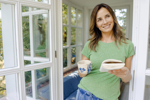Smiling mature woman at home with book and coffee mug - KNSF04623