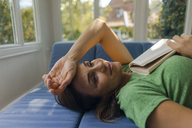 Smiling mature woman lying on couch at home with book - KNSF04626