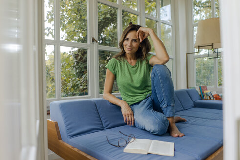 Smiling mature woman sitting on couch at home with book - KNSF04629