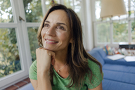 Smiling mature woman on couch at home looking away - KNSF04641