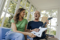 Happy mature couple sitting on couch at home with toy electric guitar - KNSF04647