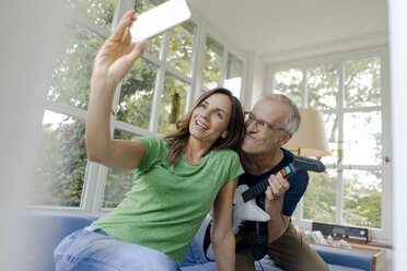 Happy mature couple taking a selfie at home with man playing toy electric guitar - KNSF04650
