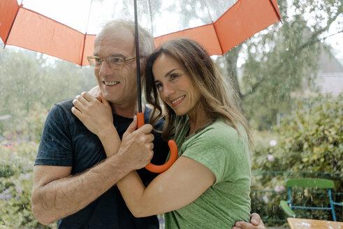 Smiling mature couple standing in rain under umbrella - KNSF04659