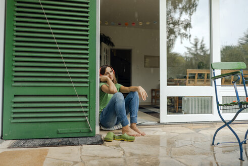 Mature woman sitting on wet terrace listening to music with headphones - KNSF04662