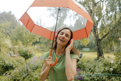 Happy mature woman standing in rain under umbrella listening to music with headphones - KNSF04665