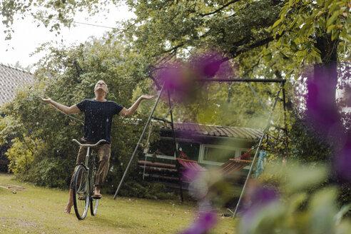 Mature man with bicycle enjoying summer rain in garden - KNSF04668