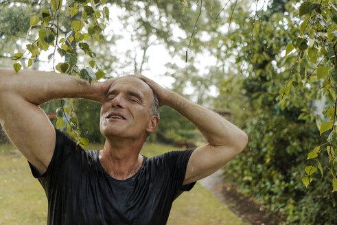Smiling mature man enjoying summer rain in garden - KNSF04671