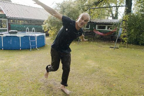 Portrait of carefree mature man enjoying summer rain in garden - KNSF04674