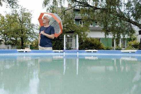 Mature man standing in summer rain in garden at swimming pool holding umbrella - KNSF04677