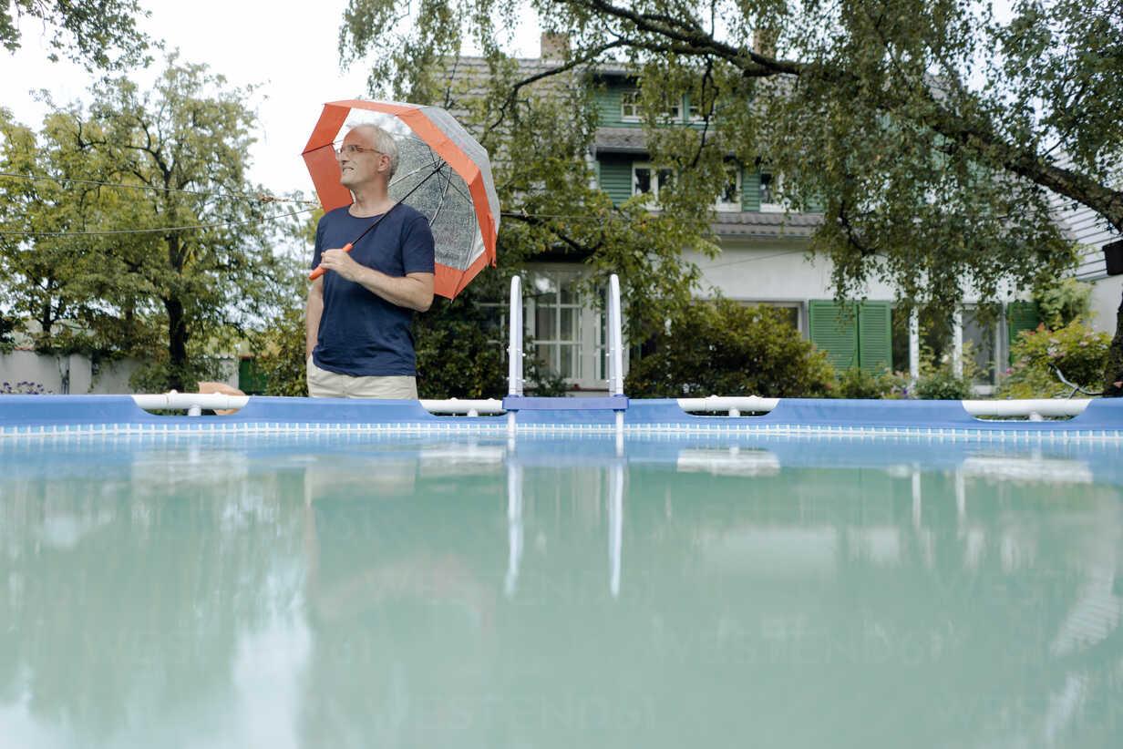Mature man standing in summer rain in garden at swimming pool holding umbrella - KNSF04677 - Kniel Synnatzschke/Westend61