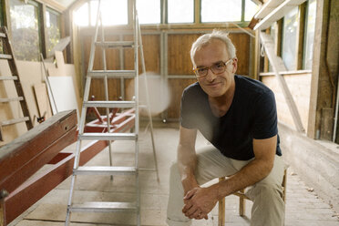 Portrait of a confident mature man sitting in his workshop - KNSF04680