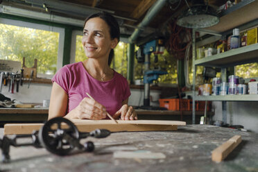 Smiling mature woman at workbench in her workshop - KNSF04683