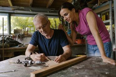 Mature woman watching man working in workshop - KNSF04692