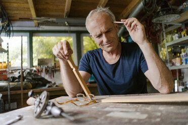 Mature man at workbench in his workshop thinking - KNSF04695