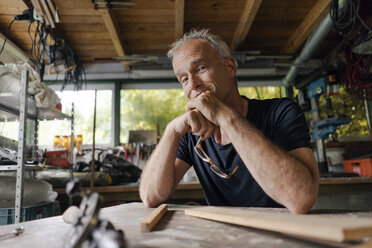 Portrait of confident mature man at workbench in his workshop - KNSF04698
