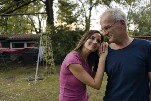 Smiling mature couple in garden of their home - KNSF04701