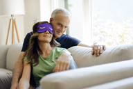 Smiling mature couple sitting on couch at home with woman wearing eye mask - KNSF04707