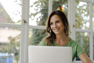 Smiling mature woman at the window with laptop - KNSF04713