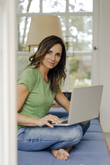 Portrait of confident mature woman sitting on couch at home with laptop - KNSF04716