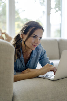 Smiling mature woman lying on couch at home using laptop - KNSF04737