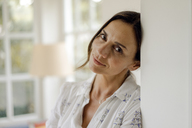 Portrait of mature woman leaning against doorframe - KNSF04758