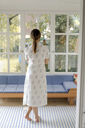 Rear view of woman standing in living room at home - KNSF04761