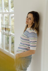 Pensive mature woman at home leaning against a wall - KNSF04764