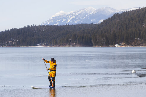 A fit male stand up paddle boards during the winter on Whitefish Lake in Montana. - AURF02652