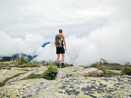 A man looks out over the clouds from the summit of Baldface Mountain, New Hampshire - AURF02688
