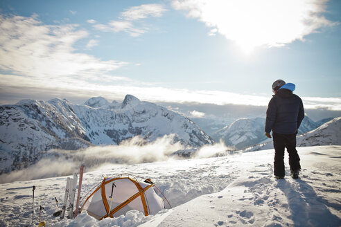A man stands on Llama Peak above his tent in British Columbia, Canada. - AURF02700