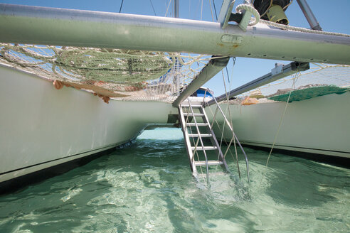 A drop-down aluminum staircase leads up to the deck of a catamaran boat. - AURF02922