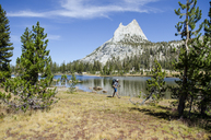 A young man walks past Cathedral Lake during a 27.3 mile backpacking trip from Tuolumne Meadows to Yosemite Valley, California. - AURF02988