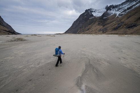 Female backpacker walks across the vast sands of Horseid beach, Moskenes├©y, Lofoten Islands, Norway - AURF03111