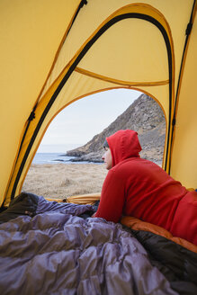 Female backpacker looks out of tent while wild camping at Horseid beach, Moskenes├©y, Lofoten Islands, Norway - AURF03114