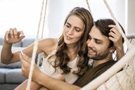 Couple in hanging chair at home looking at tablet - JOSF02552
