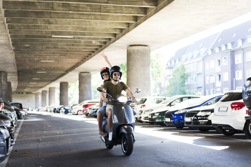 Happy couple riding motor scooter at underpass - JOSF02561