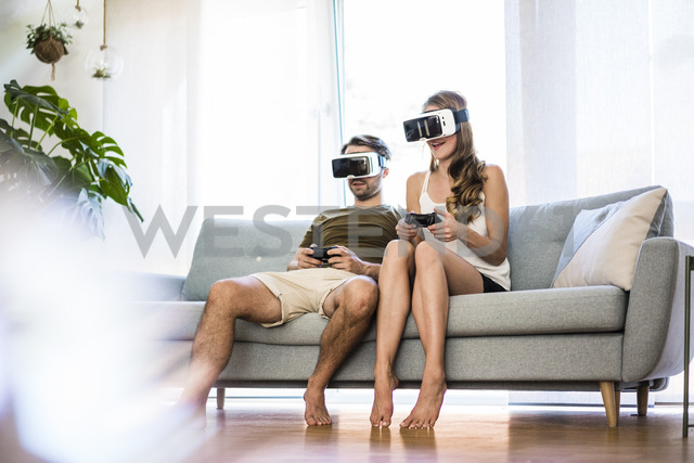 Couple sitting on couch at home wearing VR glasses playing video game - JOSF02564