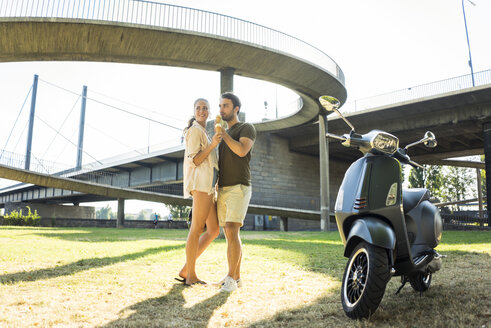 Happy couple with motor scooter in summer eating ice cream - JOSF02567