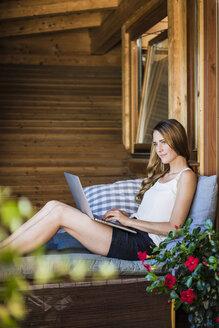 Woman relaxing on balcony using laptop - JOSF02576
