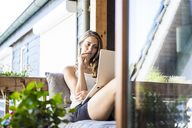 Smiling woman on balcony using laptop - JOSF02582