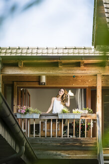 Portrait of smiling woman standing on balcony - JOSF02591