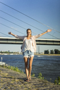Portrait of carefree woman at the riverside in summer - JOSF02603