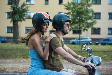Couple riding motor scooter in the city - JOSF02606