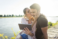Couple kissing at the riverside in summer holding tablet - JOSF02618