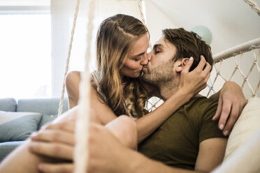 Affectionate couple kissing in hanging chair at home - JOSF02624