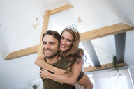 Portrait of happy couple at home with woman wearing tiara - JOSF02627